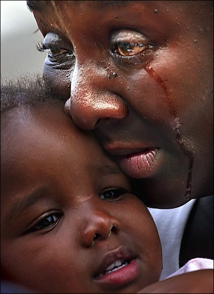 08/31/05 Matt Rourke/AMERICAN-STATESMAN At the intersection of I-10 and N. Causeway Blvd in Metairie Louisiana on Wednesday August 31, 2005 refugees from Hurricane Katrina wait for evacuation. As Shelia Dixon of Gentilly weeps she tells her tells her 18-month baby Emily Dixon Òregardless of what this looks like, this isnÕt the end.Ó Dixon and her family took their boat from their home to I-10 were the were evacuated by helicopter. The boat was left behind for other to use.